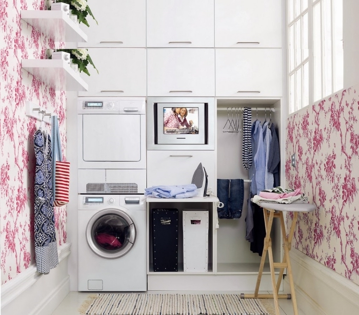 meuble buanderie de bois, déco laverie avec papier peint rose et armoires blanches, aménagement buanderie dans un placard blanc avec rangement de vêtement ouvert