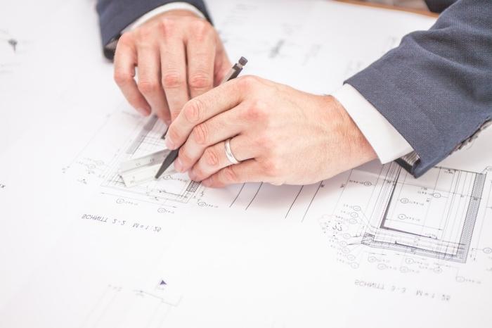 architecte qui rédige un compte-rendu de chantier avec modifications au niveau de la construction en version papier