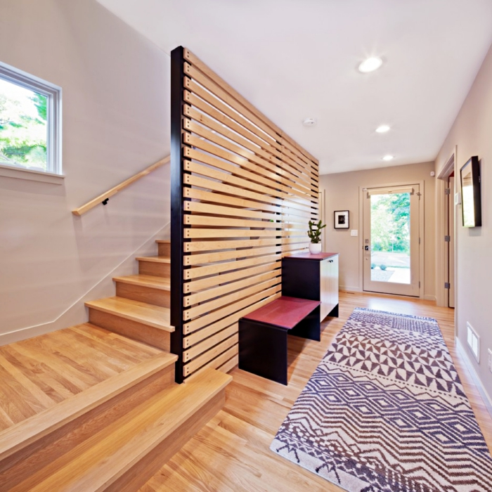 modèle de paroi en bois et noir, aménagement de couloir aux murs beige avec plafond blanc et tapis blanc et noir à design géométrique
