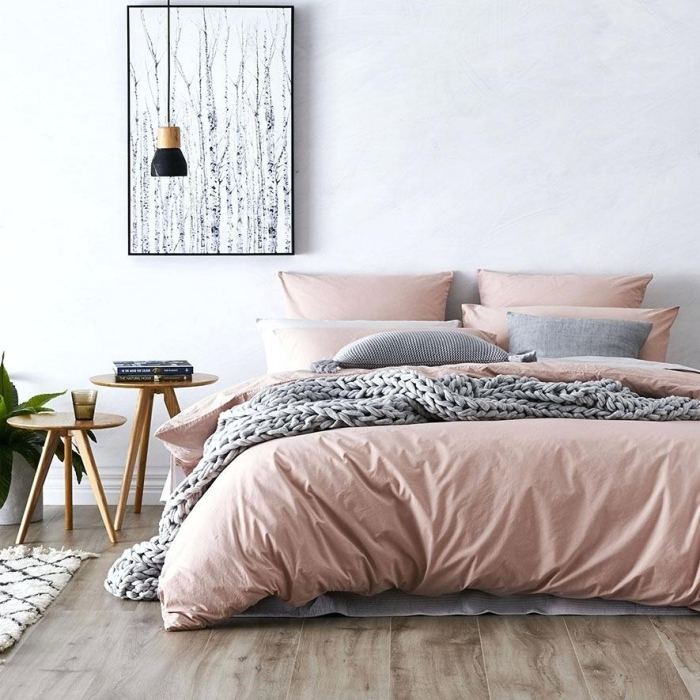 modèle de chambre rose et gris aux murs blancs avec parquet de bois foncé, déco de grand lit au linge rose poudré et coussins gris