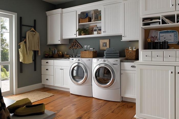 aménagement de buanderie aux murs gris clair avec plafond blanc et parquet de bois marron, déco en gris et blanc