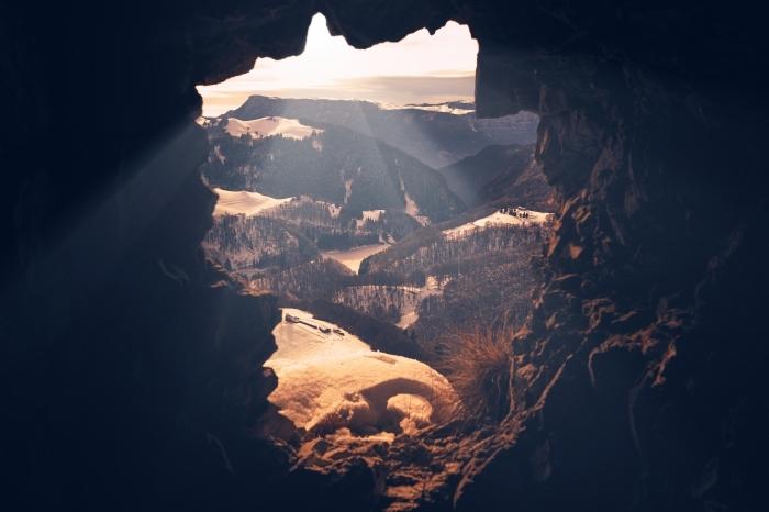 image fond d écran sombre avec un paysage d'oeil d'oiseau, vue d'une grotte vers les montagnes et les champs verts