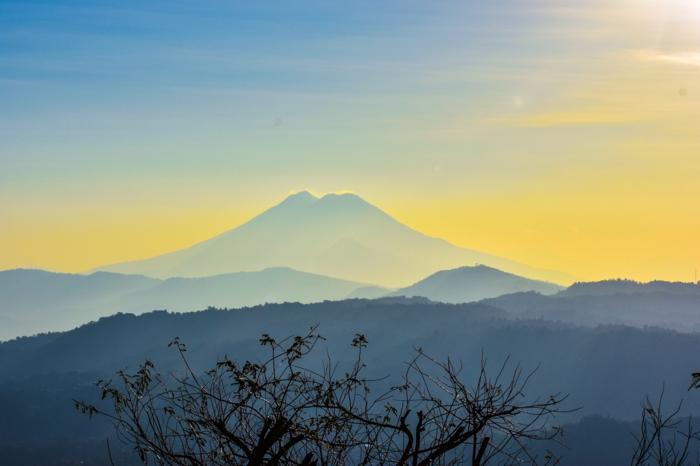 beau paysage, iles paradisiaques, montagne sur le fond d'un ciel serein, ciel en jaune, silhouettes d'arbres noires et des silhouettes de sommets d'arbres