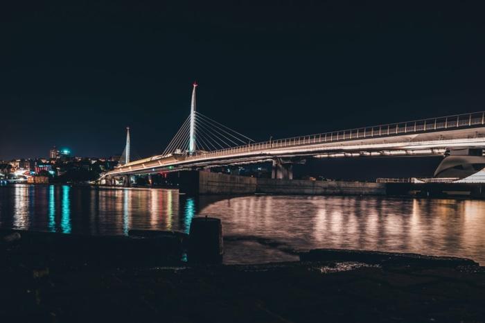 paysage de reve, pont New York, lumières bleues qui se reflètent dans l'eau, fond ecran paysage, beau paysage, gratte-ciels a l'horizon, ciel bleu foncé