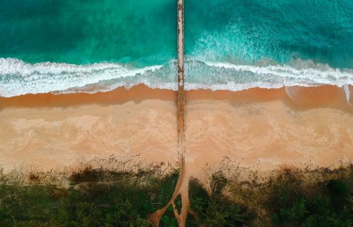 destination paradisiaque, océan aux eaux vertes transparentes avec des ondes blanches, sable beige, vue d'en haut d'un pont de promenade qui entre dans l'océan