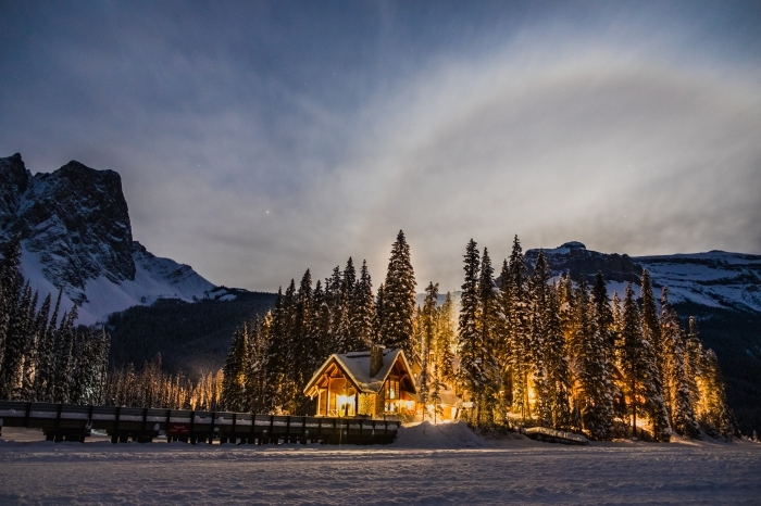 photo d'une cabine de bois dans la forêt enneigée aux arbres conifères au coeurs de montagnes, fond d écran wallpaper