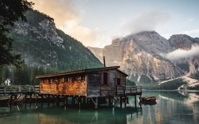 photo d'une maison en bois au bord de lac et dans les montagnes pour un fond d écran paysage au lever du soleil