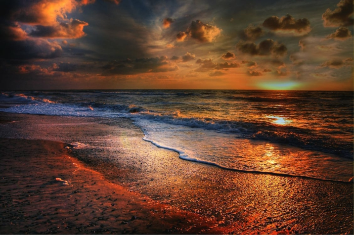 ciel au coucher du soleil en tonalités rouges et oranges, vagues tranquilles, ciel nuageux, lumière irréelle au-dessus de la mer