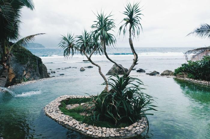 petit îlot créé par l'homme, eaux transparentes vertes, palmes vertes, horizon brumeux, journée nuageuse, ambiance cool