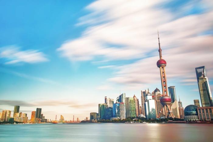 paysage urbain, endroit paradisiaque avec des gratte-ciels au design extravagant, eaux tranquilles, nuages rosés, ciel bleu