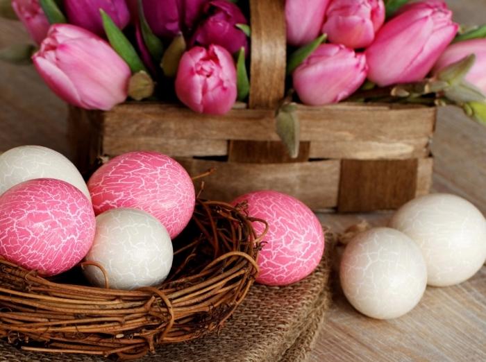 table de bois avec panier aux tulipes rose et noeud d'oeufs colorés en rose et blanc à design oeuf brisé