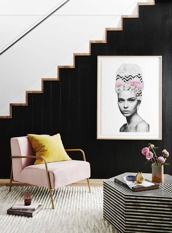 salon au mur noir avec escalier blanc et bois, deco rose poudré avec un fauteuil à finition doré et bouquet de roses