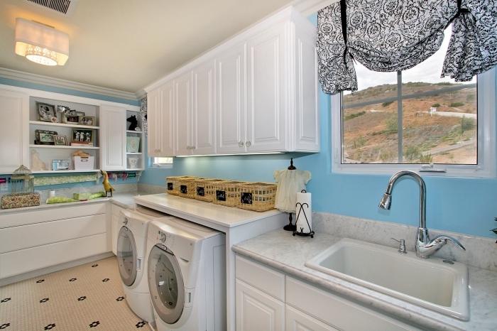 décoration intérieure aux murs bleu clair avec plafond blanc et petite fenêtre, meuble buanderie blancs sans poignées