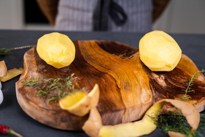 peler des pommes de terre pour concocter un repas du soir simple, pomme de terre farcie au four