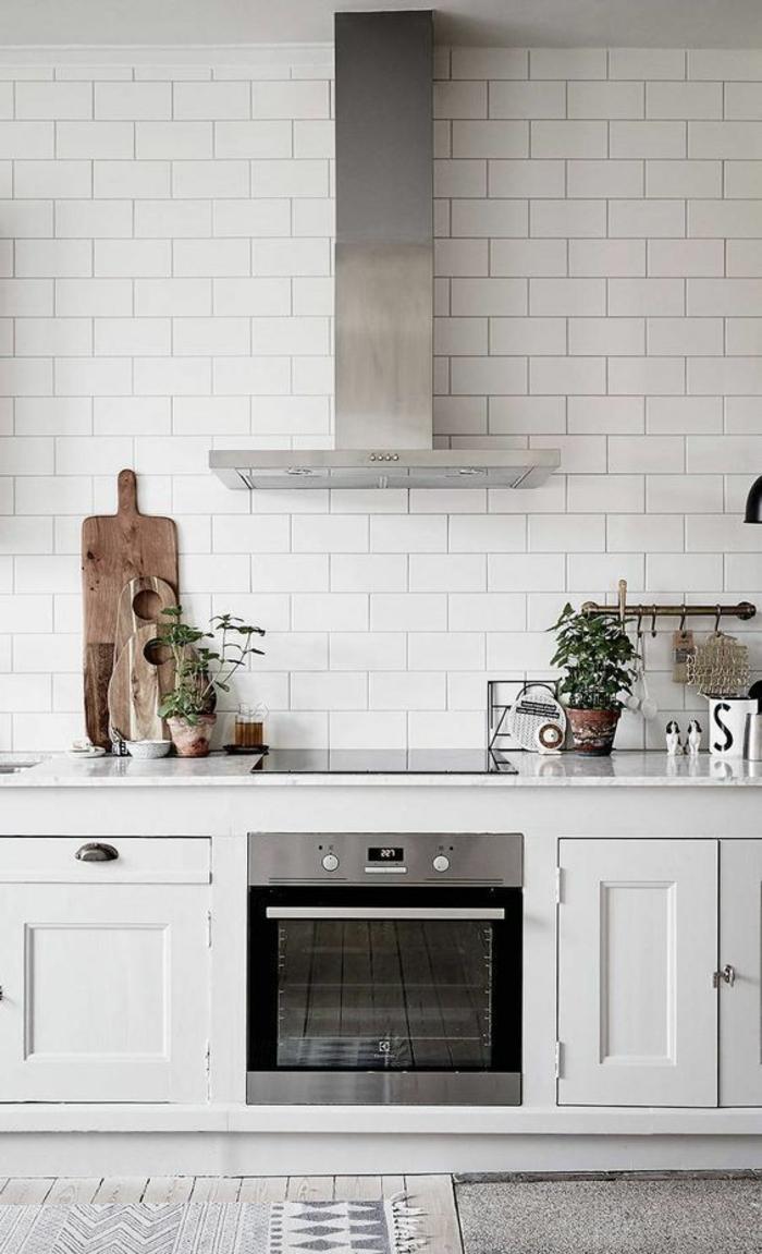 cuisine aménagée pas cher, murs en briques blanches, meubles blancs, aspirateur surface brillante métal couleur argent, parquet couleur grise avec tapis en blanc et gris avec des motifs losanges