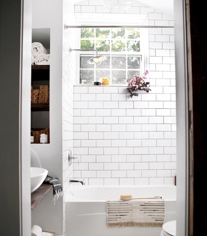 petite salle de bain avec baignoire blanche, carrelage metro blanc, niche murale avec rangements, lavabo sur une planche bois rustique