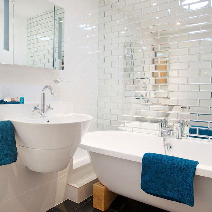 exemple petite salle de bain avec baignoire blanche sur pieds en bois lavabo blanc et serviettes de toilettes argent, sol carrelage gris anthracite