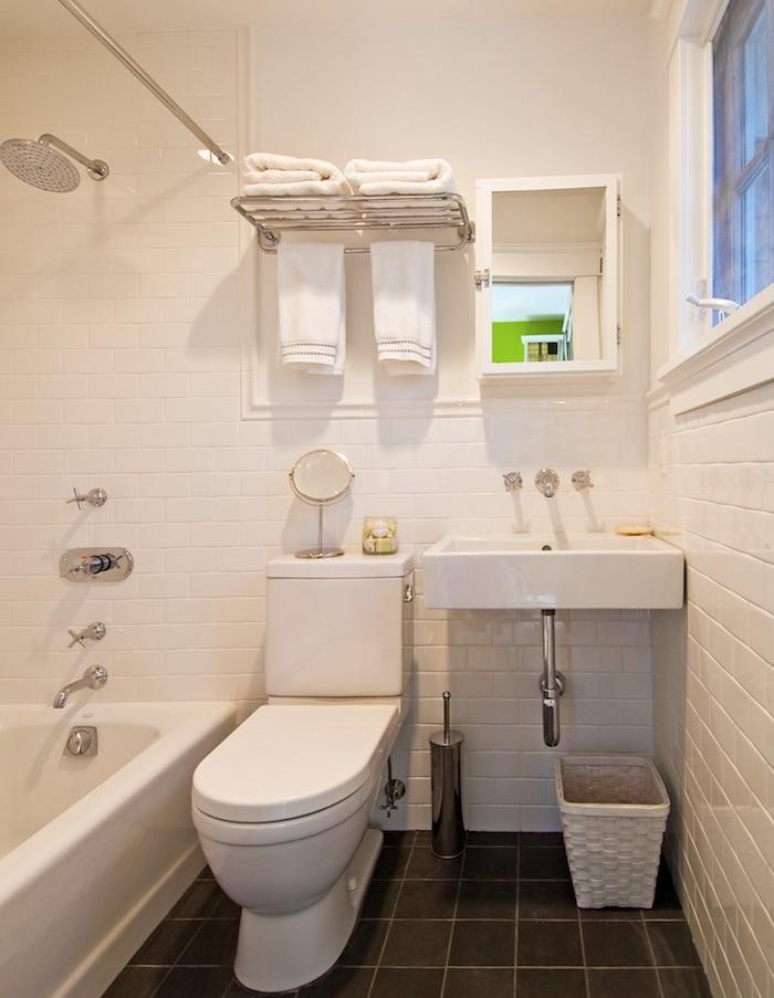 amenagement de petite salle de bain en longueur avec sol carrelage gris anthracite, mur carrelage blanc, baignoire à poser blanche, wc et lavabo blanc