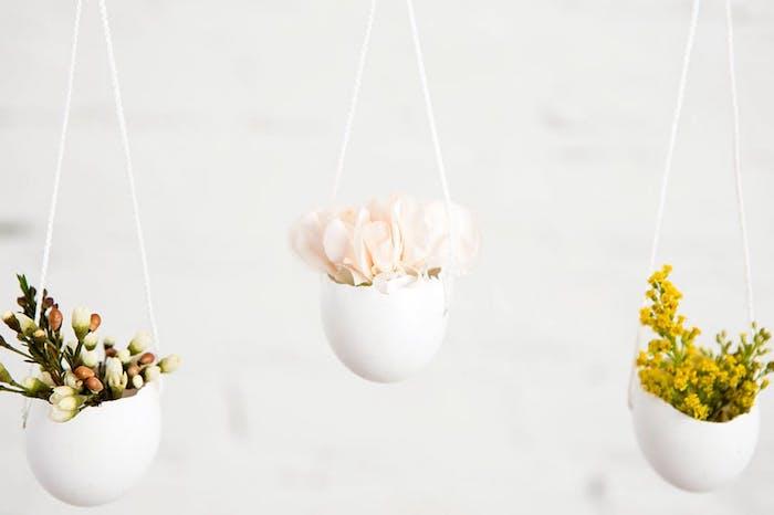 pot de fleurs en coquille d oeuf suspendu à un fil blanc avec de petits bouquets à l intérieur, deco paques originale