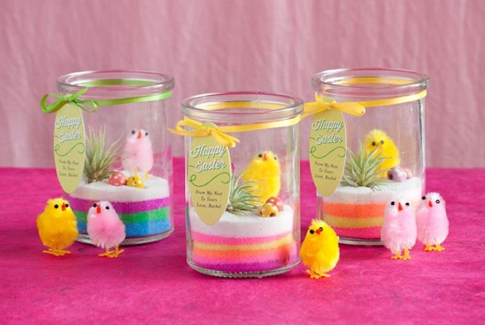 terrarium en bocal de verre avec du sable coloré, plante artificielle et petit poussin jouet, activité de pâques originale