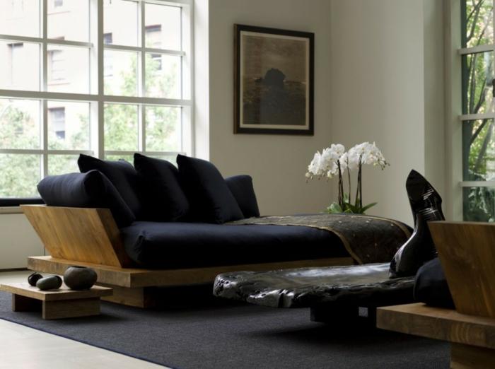 salon avec tapis gris nuance fumée, fenêtres hautes avec des cadres blancs, canapé en bois rude avec des coussins noirs et matelas noir , petite table basse en bois massif avec des pots noirs décoratifs en style ethnique