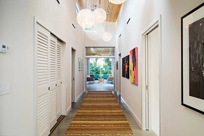 quelle couleur pour agrandir un couloir, intérieur aux murs blancs décorés de peintures et plafond de bois, carrelage de sol gris avec tapis marron