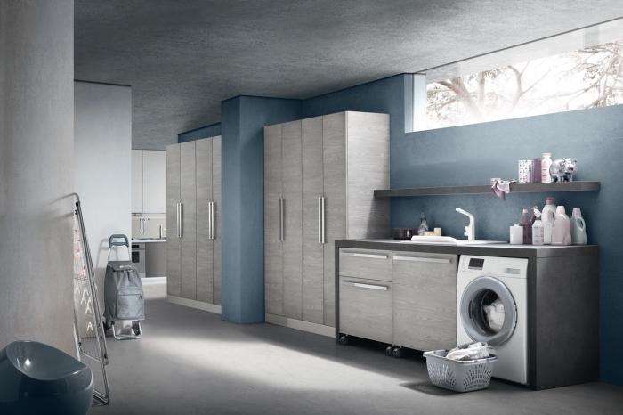 intérieur moderne aux couleurs foncées avec murs bleus et plafond à design béton gris, meubles de bois clair et foncé