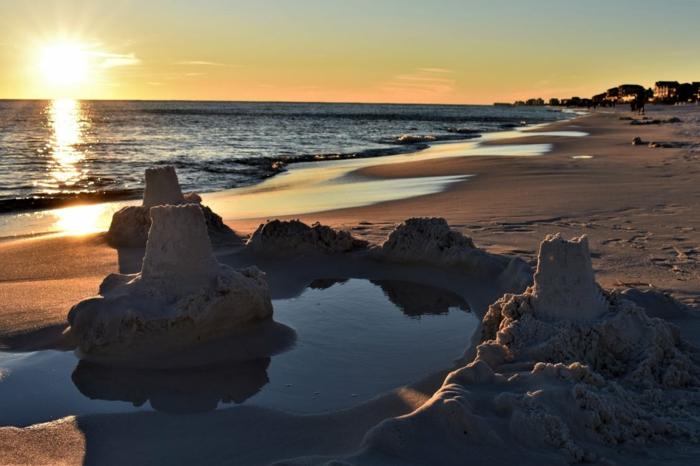 paysage de reve, paysage paradisiaque, plage avec des châteaux de sables au coucher du soleil, eaux brillantes, plage déserte, petit oasis avec château rempli d'eau marine