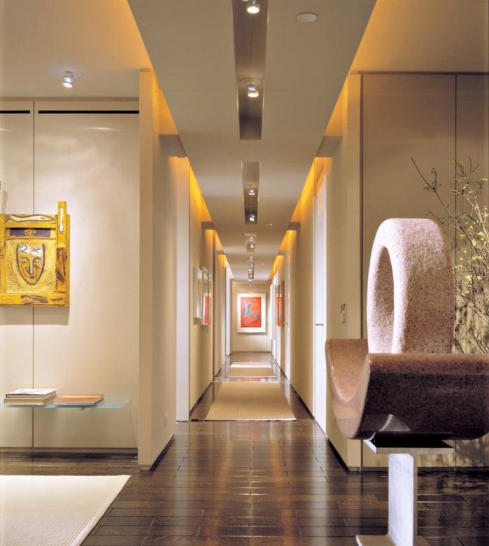 modèle de deco entree aux couleurs et finitions moderne avec parquet de bois foncé et objets décoratifs en or