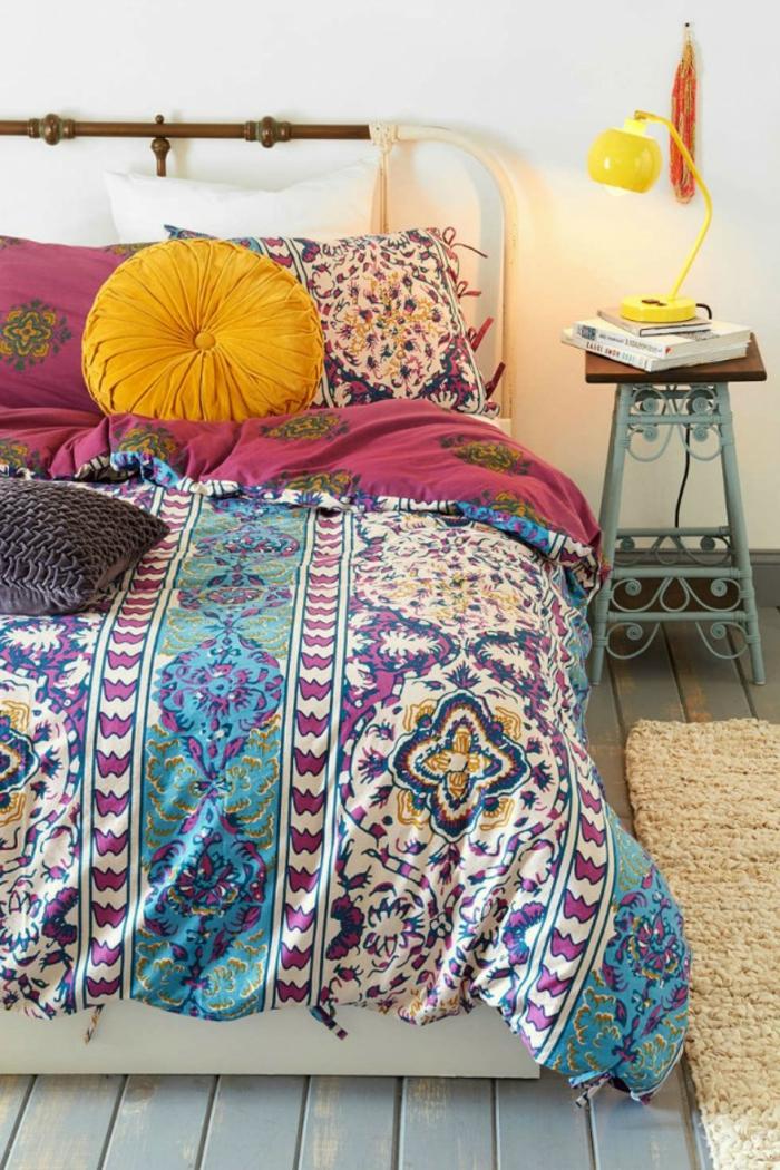 lit bohème, coussins déco, tabouret shabby, lampe jaune, tapis beige, linge de lit en joyeuses couleurs