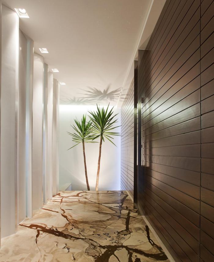 ambiance luxueuse dans un couloir au plafond blanc et plancher beige et marron, plantes vertes dans l'intérieur