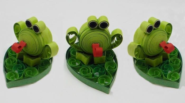 pliage de papier facile, trois grenouilles vertes en papier assises sur leurs feuilles