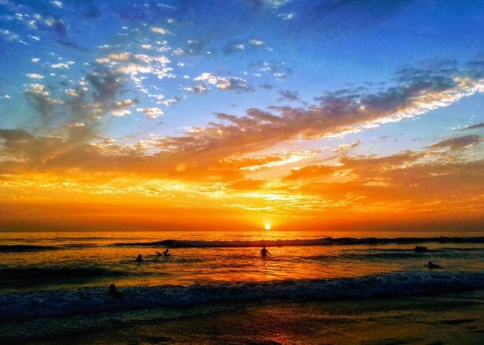 destination paradisiaque, plage en couleurs vives rouge et orange, petits nuages blancs, quasi transparents, ondes blanches