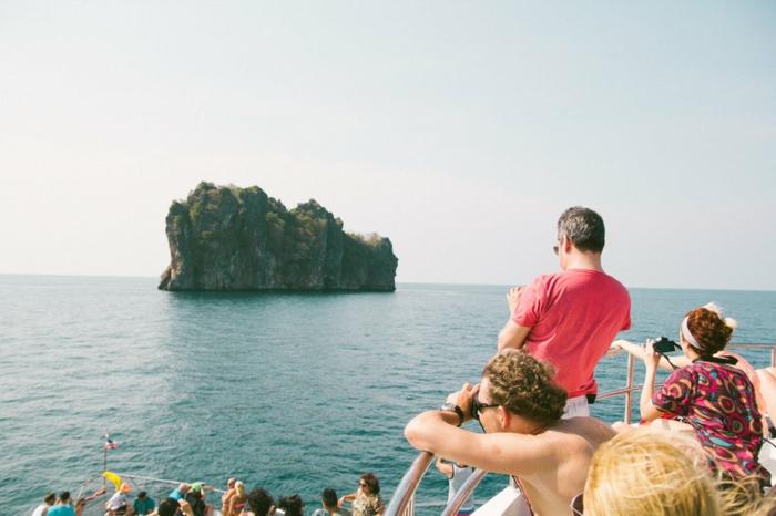 iles paradisiaques, paysage paradisiaque, îlot au milieu de l'océan, eaux bleues, touristes sur un bateau qui prennent des photos