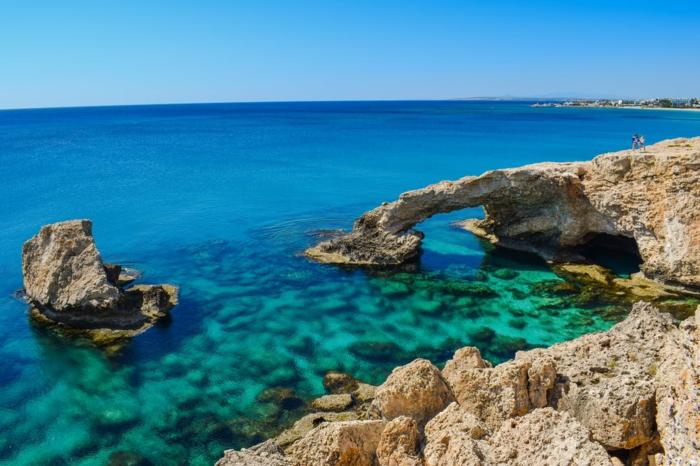 mer azur avec des rochers argileux, horizon en bleu et vert, fond ecran paysage, ciel en bleu pastel, nuances vertes et bleues de l'eau
