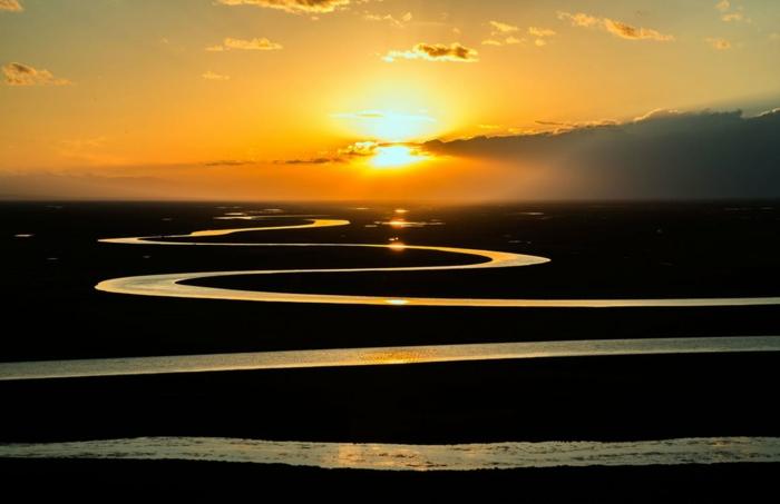 fond ecran paysage, canaux d'eau au coucher du soleil, ciel orangé, nuages en gris fumée, paysage de moment magique en noir et orangé