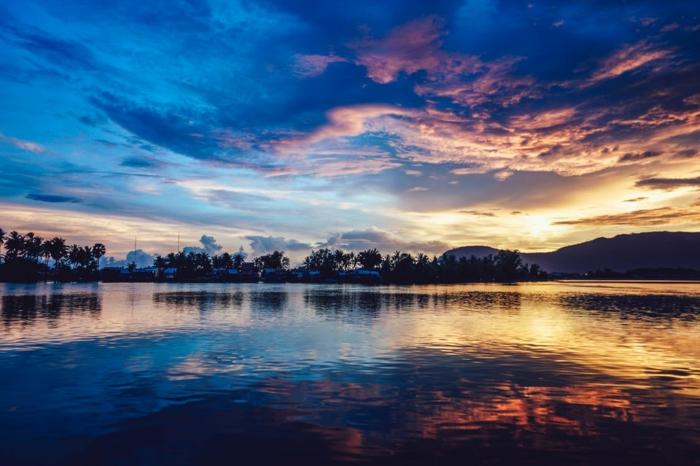 paysage paradisiaque en bleu et violet, eaux légèrement ondulantes, silhouettes de palmes a l'horizon, nuances magiques, montagnes en violet