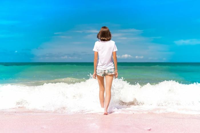 une fillette qui entre dans la mer, en levant le pied sur l'onde mousseuse qui arrive sur la plage, horizon en bleu et vert, nuages blancs, sable beige