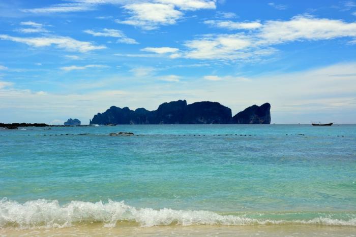 fond ecran paysage, beau paysage, silhouettes noires de montagnes rocheuses su le fond du ciel bleu-vert, barque de pêcheurs qui nage au lointain
