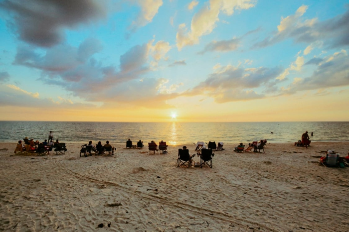 destination paradisiaque, plage au coucher du soleil, ciel bleu, touristes couchés sur leurs chaise-longues, des traces de pieds sur le sable