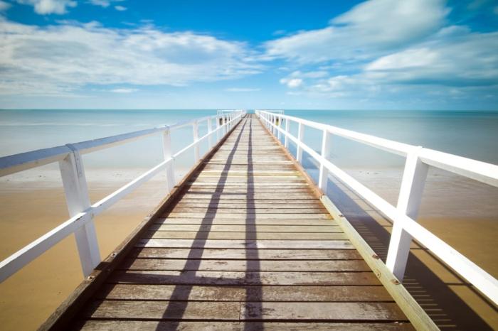 plage en été, paysage de reve, paysage paradisiaque, ciel bleu avec des nuages blancs, pont en bois peint en blanc qui va vers l'horizon, mer calme