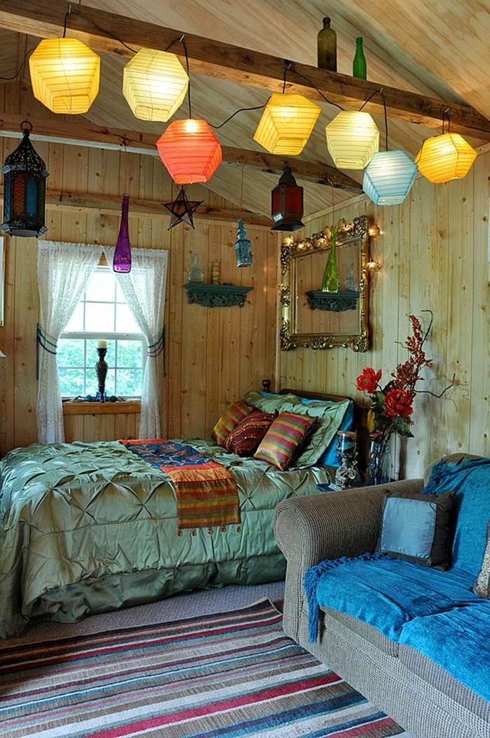 chambre gypsy à deco boheme, grand sofa bleu, lampes suspendues, plafond et murs en bois, tapis à rayures