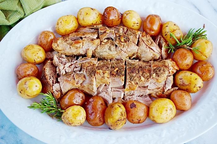 repas entre amis au poulet cuit au four avec garniture de petites pommes de terres aux herbes vertes et fraîches