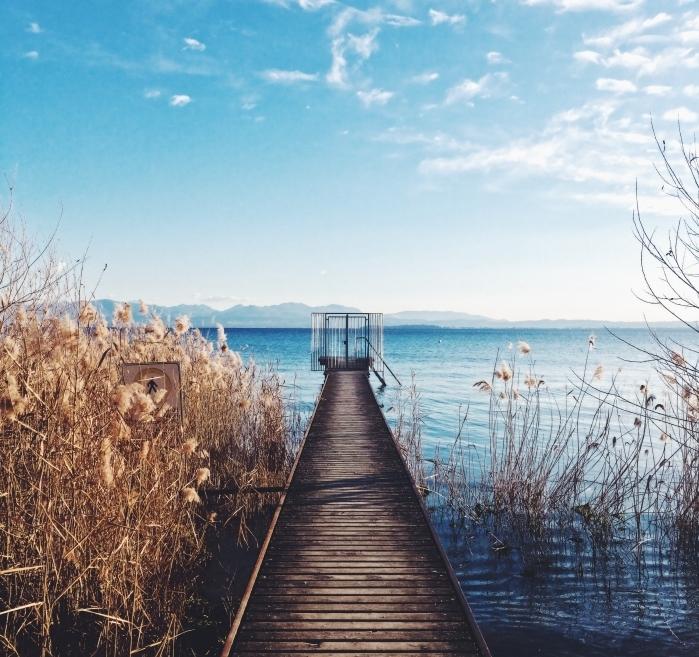 photo avec fond d écran beau, pont de bois au-dessus d'un lac turquoise qui donne une vue vers les montagnes