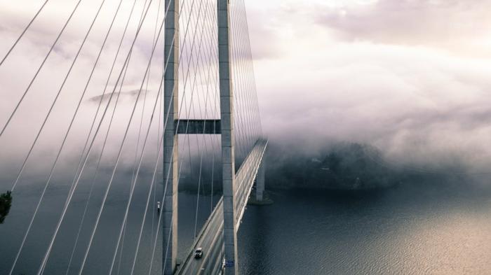 une image de pont perdu dans la brume, effet de paysage paradisiaque mystérieux, voitures qui passent sur le pont, eaux légèrement agitées par une brize