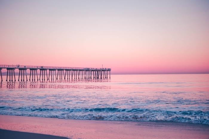 coucher de soleil au bord de la mer avec ciel rose et pont au dessus de l'eau, fond ecran paysage au bord de la mer