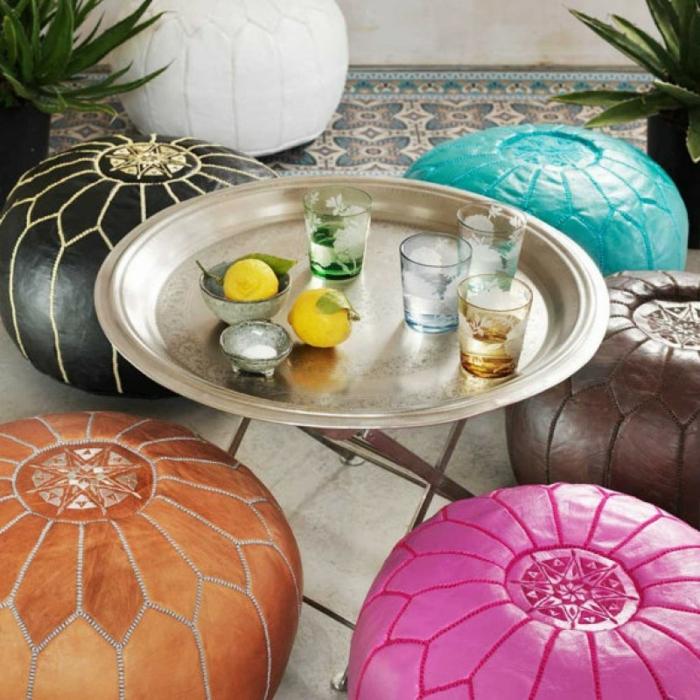 couleurs qui se mettent en joie, des poufs marocains en bleu turquoise, fuchsia, couleur tabac, marron et noir, table ronde en métal couleur argent, carrelage blanc et carrelage en style marocain