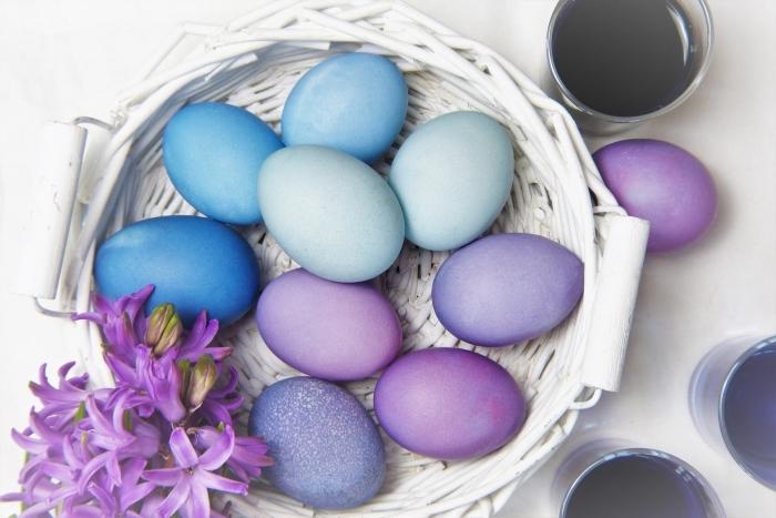 exemples d'oeuf de paque colorés en peinture alimentaire de nuances bleu et violet posés dans un panier de fibre végétal peint en blanc