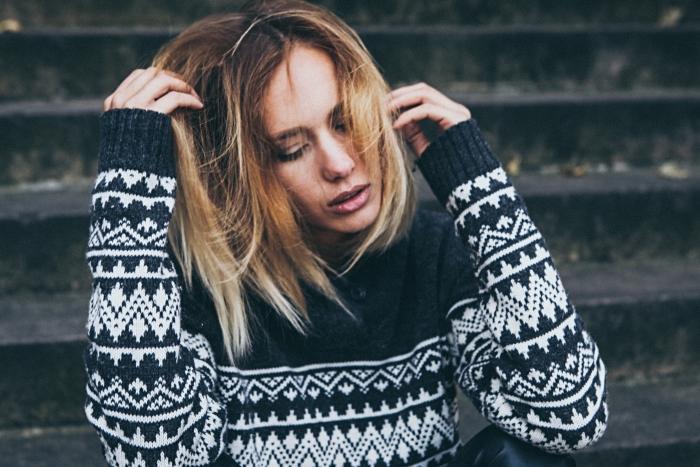 modèle de pull femme en noir avec motifs géométriques en blanc, ombré blond aux reflets cuivrés sur cheveux marron
