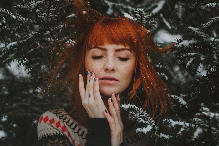 frange courte sur cheveux en carré mi long, coloration rousse, pull hiver, fond en branches de pin